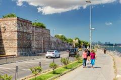 De mensen lopen langs de promenade voorbij de oude zeedijken van Co Stock Afbeelding