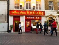 De mensen lopen langs een bezige het winkelen straat in de Chinatown van Londen Stock Fotografie