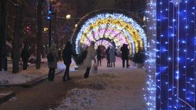 De mensen lopen langs festively verfraaide straten Op de achtergrond van mooie gekleurde slingers stock video