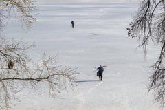 De mensen lopen langs de rivier die met ijs wordt behandeld stock afbeeldingen