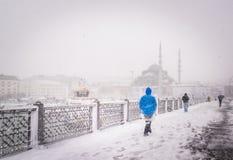 De mensen lopen op de galatabrug op een sneeuwdag in de winter Stock Afbeelding