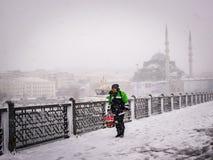 De mensen lopen op de galatabrug op een sneeuwdag in de winter Stock Fotografie