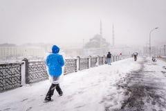 De mensen lopen op de galatabrug op een sneeuwdag in de winter Stock Afbeeldingen
