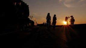 De mensen lopen op het strand tijdens zonsondergang Silhouetten van mannen, vrouwen en kinderen stock videobeelden