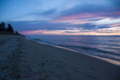 De mensen lopen op het strand van meer Baikal bij zonsondergang stock afbeelding