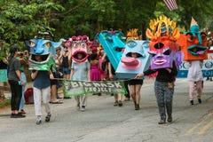 De mensen lopen in Parade die Reusachtige Creatieve Maskers op Hoofden dragen Stock Afbeelding