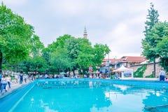 de mensen lopen rond pool bij Orhangazi-Vierkant in Slijmbeurs, Turkije stock foto