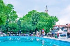 de mensen lopen rond pool bij Orhangazi-Vierkant in Slijmbeurs, Turkije stock foto's