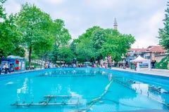 de mensen lopen rond pool bij Orhangazi-Vierkant in Slijmbeurs, Turkije stock afbeeldingen
