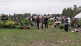 De mensen lopen tussen installaties in botanische tuinmarkt stock videobeelden