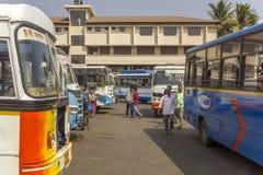 De mensen lopen tussen de multi-colored bussen in het Indische busstation royalty-vrije stock afbeelding