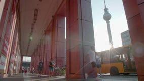 De mensen lopen voor de bus buiten Alexa Mall in Berlijn met de TV-toren op de achtergrond stock video
