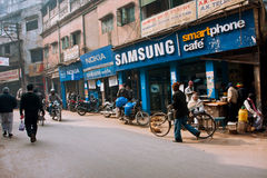 De mensen lopen voorbij de mobiele telefoonswinkels Royalty-vrije Stock Afbeelding