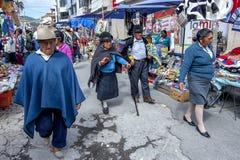 De mensen lopen voorbij de vele boxen bij de Indische markt in Otavolo in Ecuador royalty-vrije stock fotografie