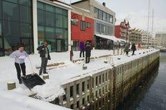 De mensen maken sneeuw schoon en lopen door de straat van Svolvaer, Noorwegen Stock Afbeelding
