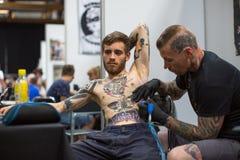 De mensen maken tatoegeringen bij de 10de Internationale Tatoegeringsovereenkomst in het Centrum congres-Expo Royalty-vrije Stock Foto