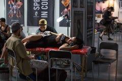 De mensen maken tatoegeringen bij de 10de Internationale Tatoegeringsovereenkomst in het Centrum congres-Expo Royalty-vrije Stock Foto's