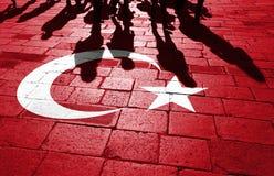 De mensen met de vlag van Turkije schilderden op de vloer Stock Fotografie