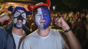 De mensen met verf op gezicht springen in verrukking aan winst van socer of voetbalwedstrijd 4k stock video