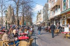 De mensen nemen een drank bij de terrassen van Het Plein dichtbij de Nederlandse Overheidsgebouwen van Haque Stock Foto's