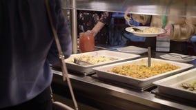 De mensen nemen voedsel bij buffet stock footage