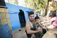 De mensen in officieuze vluchteling kamperen Stock Foto's