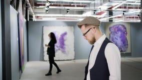 De mensen onderzoeken beelden in zaal van moderne kunstgalerie, de mens en vrouw stock videobeelden
