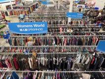 De mensen onderzoeken doorgang van kleren winkelend in de opslag van Ross met teken Stock Foto