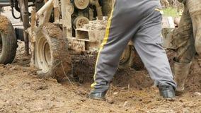 De mensen ontslaan van de modder een roestige geïmproviseerde installatie stock videobeelden