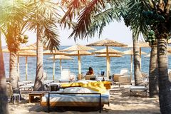 De mensen ontspannen als zitkamervoorzitter tegen de achtergrond van palmen en rietparaplu's zonlicht in het Overzees wordt weers stock afbeelding