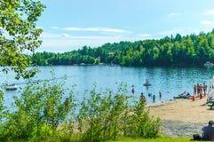 De mensen ontspannen op het meerstrand in de zomer Stock Foto's