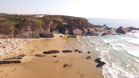 De mensen ontspannen op het strand Zambujeira DE Mar dichtbij de rotsen luchtmening stock video