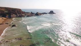 De mensen ontspannen op het strand Zambujeira DE Mar dichtbij de rotsen luchtmening stock footage