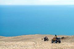 De mensen op ATVs en motorfietsen, gaan naar de kant van de reservoirmeren op droog Stock Afbeeldingen