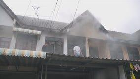 De mensen op dak helpen om een brand te doven die brandend huis i stock video