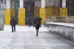 De mensen op de brug van de Patriarch in sneeuw stormen Stock Afbeelding