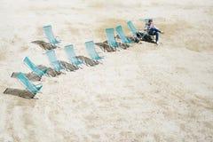 De mensen op ligstoelen in het zand lezen een boek Stock Fotografie