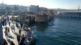De mensen overbevolken het lopen op Eminonu-bazaar en pijlerdok stock footage