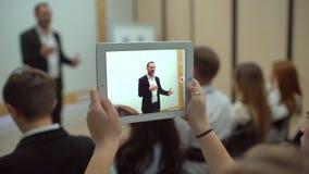 De mensen overhandigen het gebruiken van tabletcomputer bij een commerciële vergadering, een seminarie of een lezing de Professio stock videobeelden