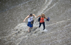 De mensen proberen om een overstroomde weg te kruisen   Stock Foto