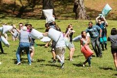 De mensen raken elkaar met Hoofdkussens op de Dag van de Hoofdkussenstrijd Stock Afbeelding