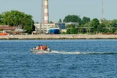 De mensen in rubberboot met motor drijven Royalty-vrije Stock Afbeelding