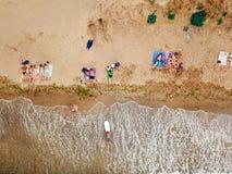 De mensen rusten op het wilde strand met hun families stock afbeelding
