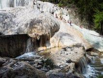 De mensen rusten op de thermische zoute watervallen van de minerale lentes van Bagni San Filippo op een zonnige dag royalty-vrije stock fotografie