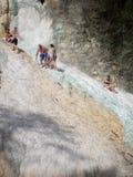 De mensen rusten op de thermische zoute watervallen van de minerale lentes van Bagni San Filippo op een zonnige dag royalty-vrije stock afbeelding
