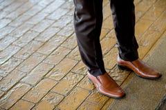 De mensen` s benen van de Hipstermanier in zwarte jeans en bruin leer Royalty-vrije Stock Foto's