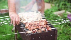 De mensen` s hand draait het vlees op de grill stock videobeelden