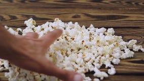 De mensen` s hand neemt handvol van popcorn van stapel die op oude houten lijst verspreid is stock video