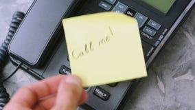 De mensen` s hand werpt document blad met inschrijving roept me op oude telefoon stock videobeelden