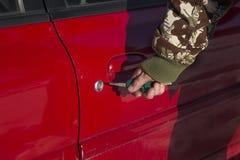 De mensen` s hand zet de sleutel in het slot van de auto Stock Foto